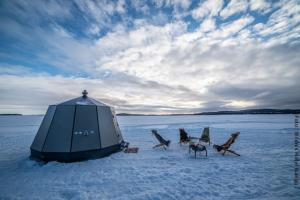 Nordlichterhütte auf zugefrorenem Inarisee